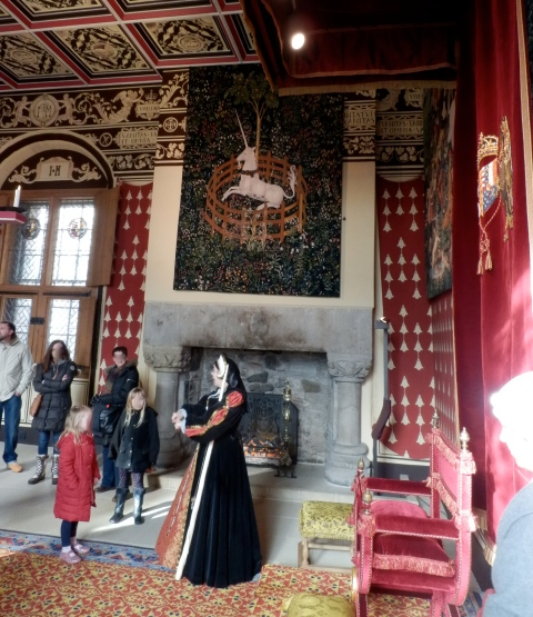 A lady in period costume gossips to visitors about daily life at the court of King James V.